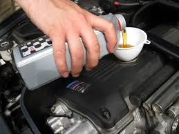 putting oil in car